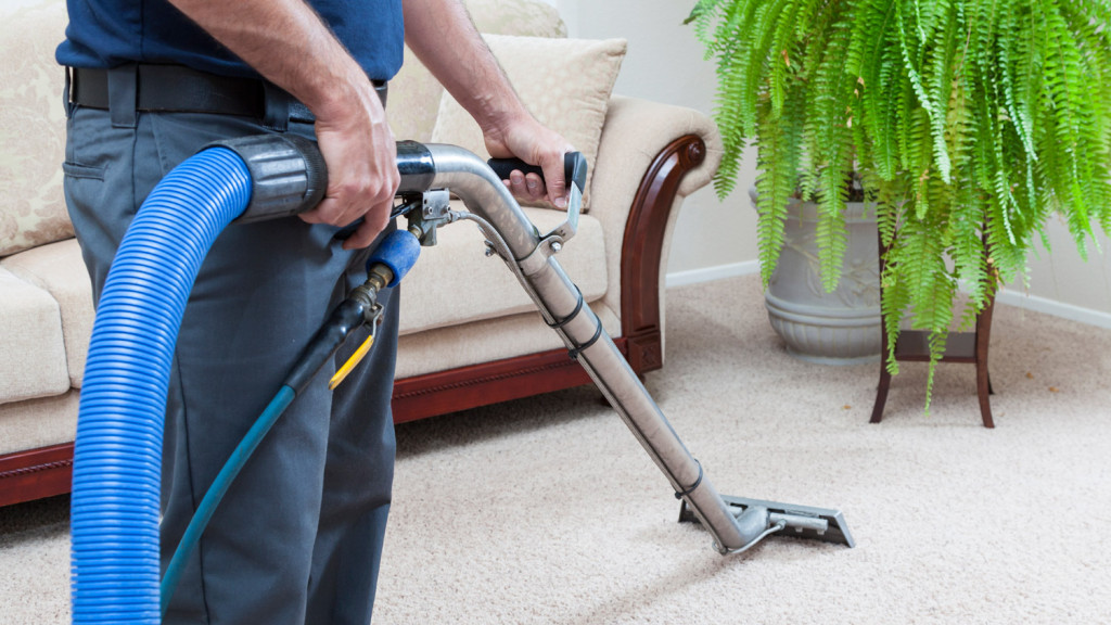 water damage restoration cairns man cleaning carpets